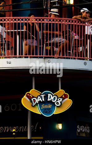 New Orleans, Louisiana - July 13, 2015: Dat Dog restaurant sign with people eating at the background. - Stock Photo