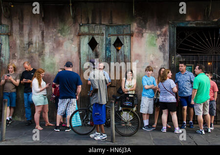 New Orleans, USA - July 13, 2015: A crowd of people stand in line for a Jazz music performance in Preservation Hall - Stock Photo