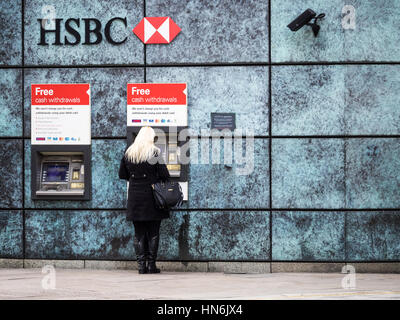 A woman uses a HSBC cash machine in Central London - Stock Photo