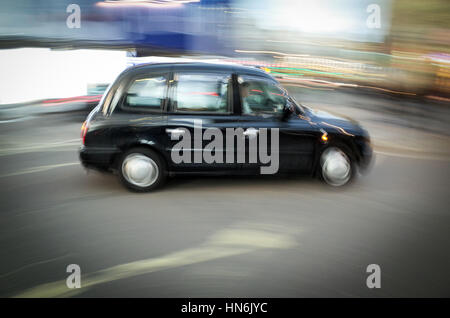 A London Taxi drives through Piccadilly Circus - Motion Blur - Stock Photo