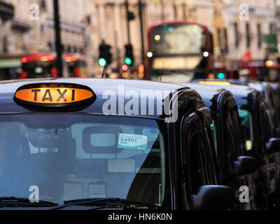 London taxis Black Cabs queue for passengers in Piccadilly, London - Stock Photo