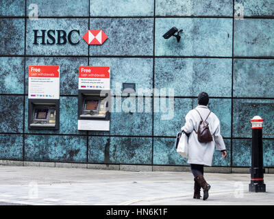 A woman walks towards HSBC cash machines in Central London - Stock Photo
