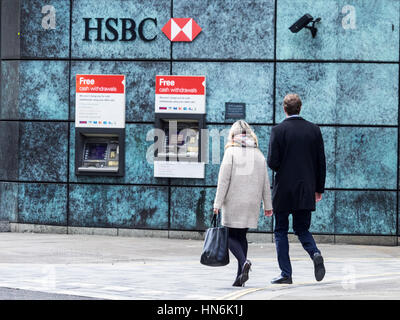 A couple walk towards HSBC cash machines in Central London - Stock Photo
