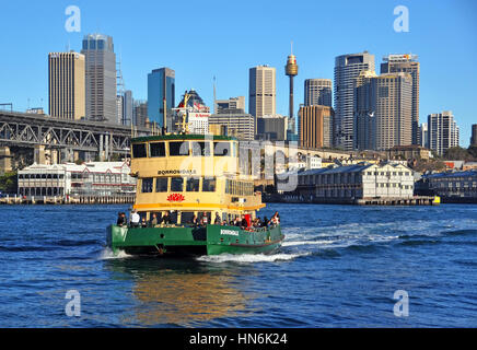 One of Sydney's famous green and yellow ferry boats crosses the harbour from Darling Harbour to McMahons Point. - Stock Photo