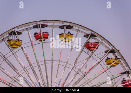 Santa Monica, USA - December 27, 2015: Ferris wheel at Pacific Park with gondolas during sunset - Stock Photo
