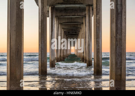 Symmetrical shot under Scripps Pier with waves during sunset in La Jolla, San Diego, California - Stock Photo