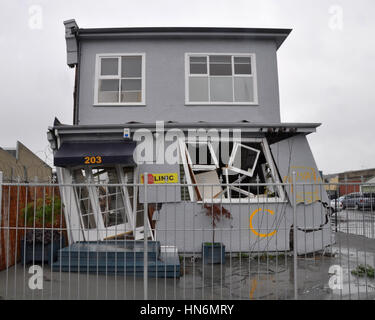 Christchurch, New Zealand - March 20, 2011: A house in the east of the city leans precariously after the 22 Februray - Stock Photo