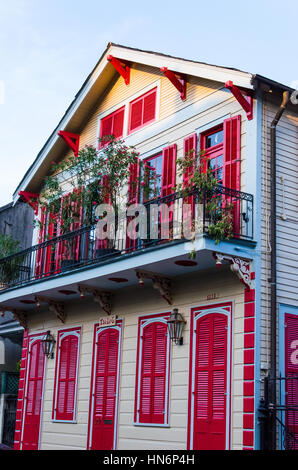 New Orleans, USA - July 13, 2015: Residential house with red doors and windows and flowers on balcony - Stock Photo