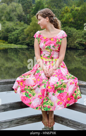 Young woman sitting by lake on railing in vintage clothing - Stock Photo