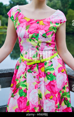 Closeup of young woman standing by lake on railing in vintage clothing - Stock Photo