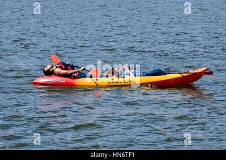 Washington DC, USA - April 12, 2015: People in tandem kayak resting and looking at phone on Potomac river - Stock Photo