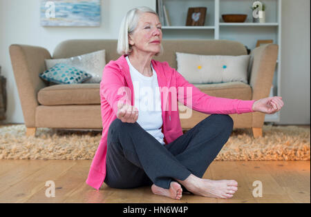 Senior woman meditating in the comfort of her home. - Stock Photo