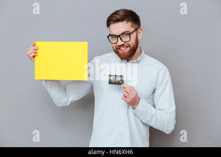 Image of attractive young bearded businessman holding copyspace blank and debit card standing over grey background. - Stock Photo
