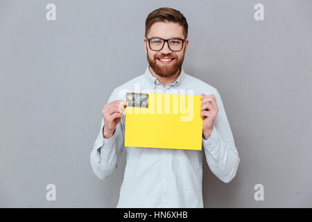 Picture of handsome young bearded businessman holding copyspace blank and debit card standing over grey background. - Stock Photo