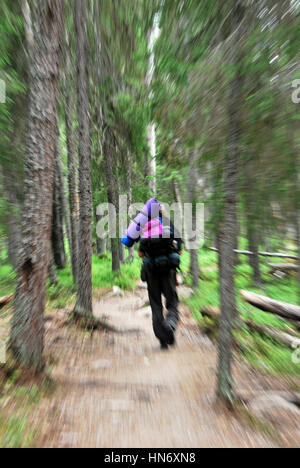 Man with a rucksack on his back running away in the scandinavian forest - Stock Photo