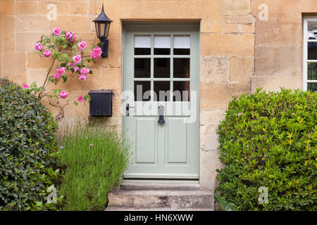 Light green wooden doors in an old traditional English lime stone cottage surrounded by climbing pink roses, lavender, - Stock Photo