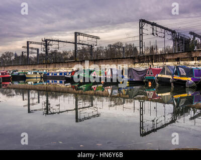 Canal boats moored on Regent's Canal with Train lines into St Pancras Station in background, London, UK. - Stock Photo