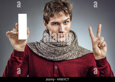 Man holding white box of medicine and shows two fingers. Photo of unhealthy man wrapped scarf. Health care concept - Stock Photo