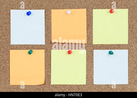 Six various and blank sticky notes on an office cork bulletin board. - Stock Photo
