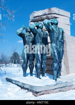 Soviet salute, one of the many statues in a Snow covered Memento Park, Budapest.. - Stock Photo