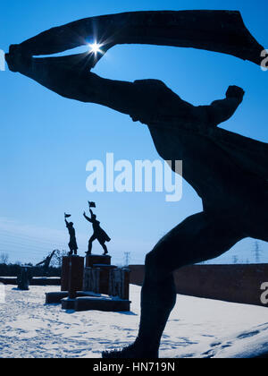 The memorial to the  Hungarian Socialist Republic, one of the statues in a Snow covered Memento Park, Budapest.. - Stock Photo