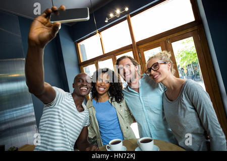 Group of friends taking a selfie from mobile phone in café - Stock Photo