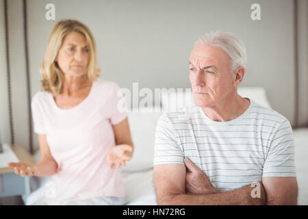 Worried senior man sitting on bed in bedroom - Stock Photo