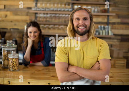 Man standing with arms crossed while waitress standing behind counter in café - Stock Photo