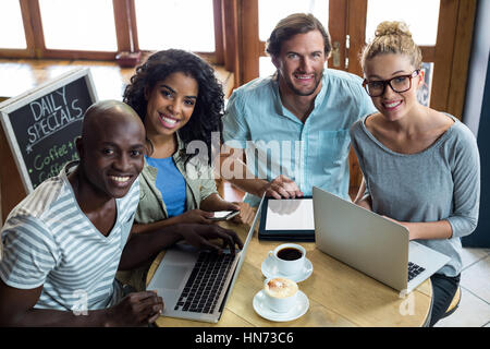 Portrait of friends using laptop and digital tablet while having coffee in café