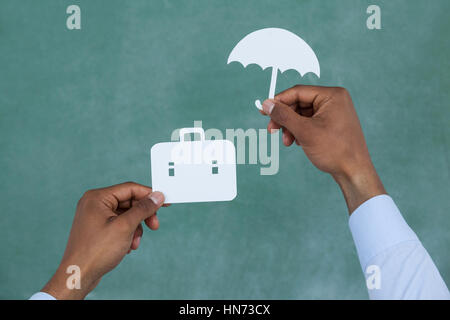 Man protecting paper cut out briefcase with umbrella on green background - Stock Photo