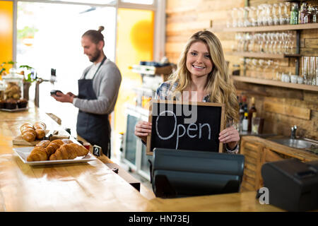 Smiling waitress standing at counter and showing slate with open sign in café - Stock Photo