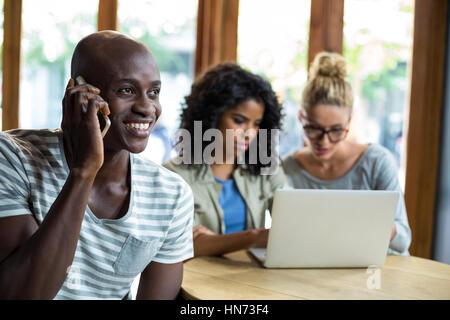 Smiling man talking on mobile phone in café