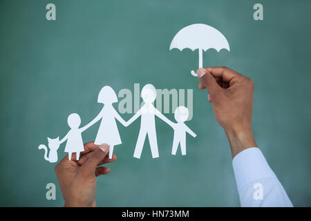 Man protecting paper cut out family with umbrella on green background - Stock Photo