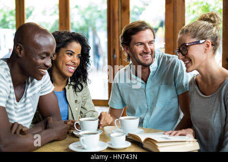Happy group of friends interacting in café - Stock Photo