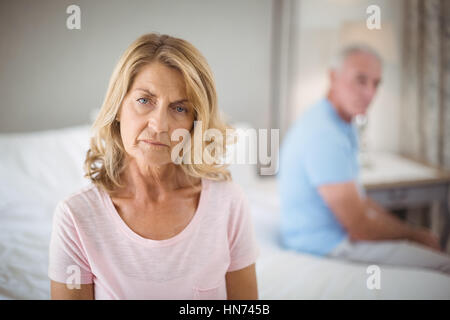 Senior couple ignoring each other on bed in bedroom at home - Stock Photo