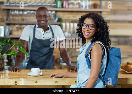 Portrait of woman and waiter smiling at counter in café - Stock Photo