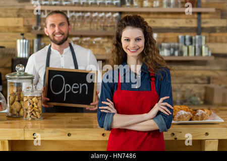 Portrait of waitress standing with arms crossed at counter in café with waiter holding open sign board in background - Stock Photo