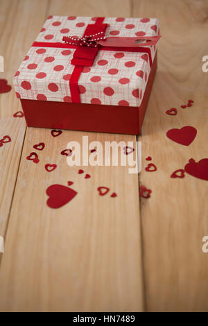Gift box surrounded with red heart decoration against wooden background - Stock Photo