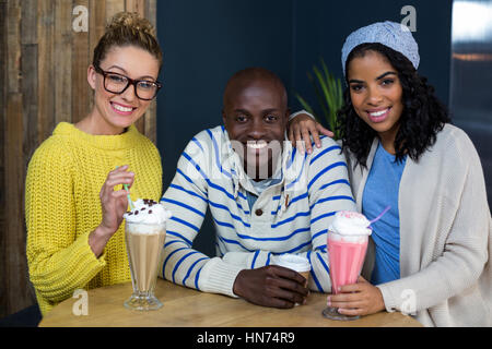 Portrait of happy friends having coffee and milk shakes in café - Stock Photo