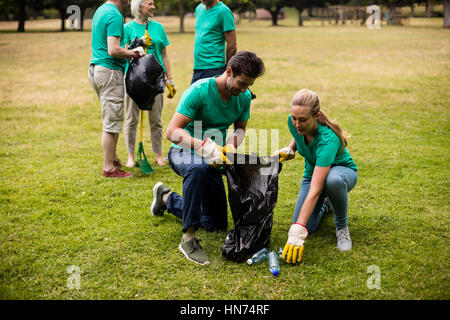 Team of volunteers picking up litter in park - Stock Photo