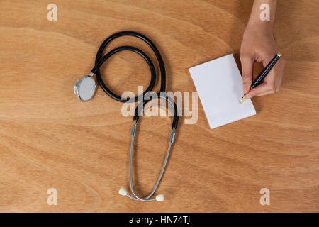 Close-up of doctor writing prescription on notepad - Stock Photo
