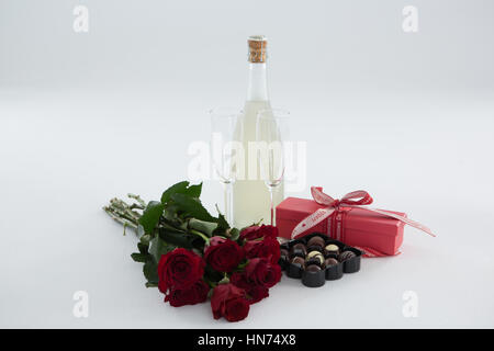 Close-up of gift, chocolate box, roses and champagne bottle on white background - Stock Photo