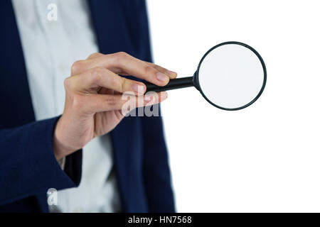 Mid section of businesswoman holding magnifying glass on white background - Stock Photo