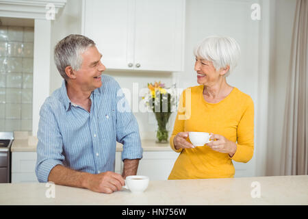 Happy senior couple interacting each other while having coffee in kitchen - Stock Photo