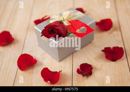 Roses and gift box surrounded by rose petals against wooden background - Stock Photo