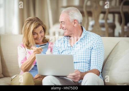 Smiling senior couple doing online shopping on laptop in living room at home - Stock Photo