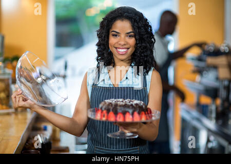 Portrait of smiling waitress holding a cake stand with chocolate cake in café - Stock Photo