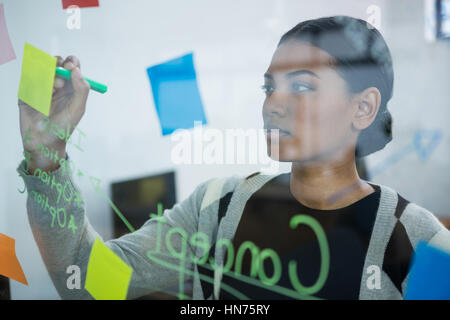 Businesswoman writing on sticky notes in office - Stock Photo