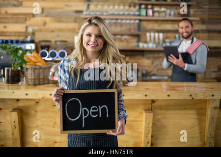 Portrait of smiling waitress showing slate with open sign in café - Stock Photo