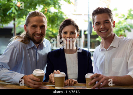 Portrait of young friends having coffee in café - Stock Photo